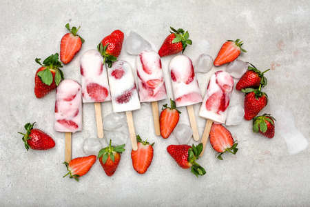 Fresh strawberry popsicle. Juicy fruit lollipops, fruity cold snack food, flat lay, top view. Stockfoto