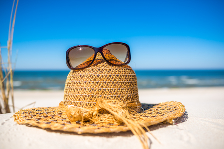 Summer beach accessories - sun hat and sunglasses on sand. Summer vacation background, Baltic Sea, Poland. Stock Photo