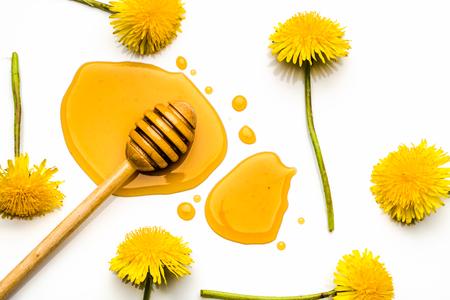 Dandelion flowers, yellow drop and honey dipper. Wild flower honey, flat lay, top view.