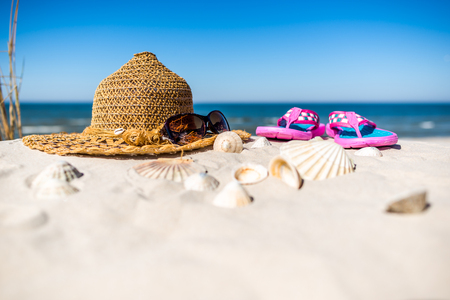 Background with vacation summer beach accessories over Baltic Sea with white sand and blue sky. Glasses, Sun hat and flip flops.