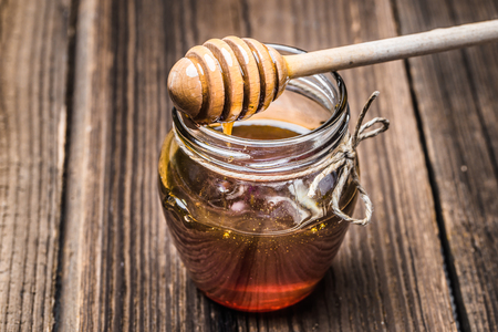 Glass jar of honey and dipper on wooden background Stock Photo