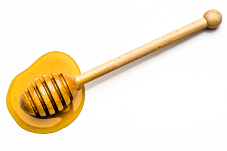 Drop of honey, top view with a wooden honey dipper isolated on white background