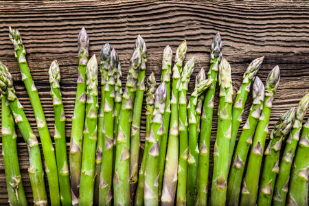 Fresh asparagus, top view on wooden table