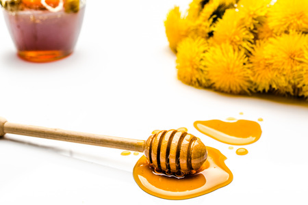 Dandelion flowers, honey dipper and glass jar of honey isolated on white background