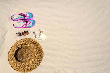 Summer accessory on sand beach, top view of sun hat, flip flop and sunglasses. Vacation background.