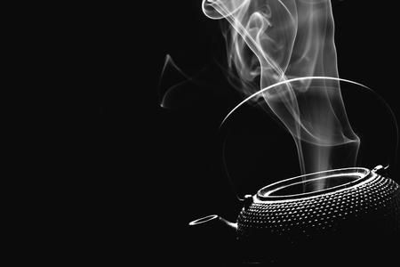 Antique teapot. Steaming tea pot on black background. Cooking concept. Archivio Fotografico - 123337127