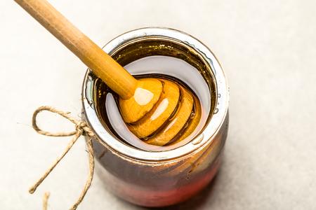 Honeydew honey jar and stick in honey on white background