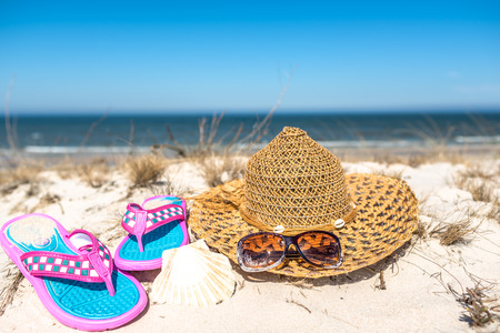 Holiday landscape of sea with summer beach accessories on sand, tourism, vacation and recreation concept