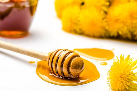 Dandelion honey - stick with drop of honey on white background Stock Photo