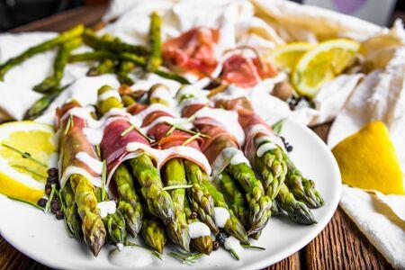 Plato italiano con espárragos cocidos envueltos con jamón prosciutto
