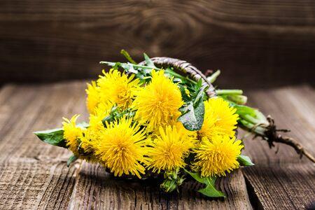 Bouquet of dandelion flowers, yellow wildflowers on wooden background