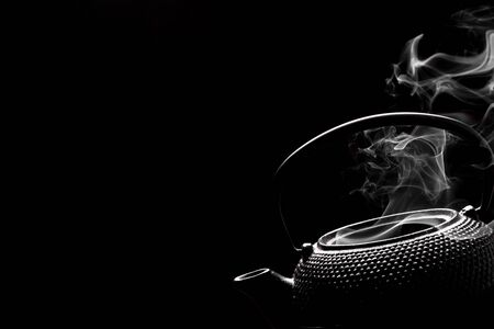 Antique rustic teapot on black background. Steaming tea pot. Cooking concept.