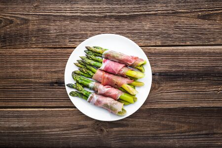Cooked asparagus. Appetizer with vegetable and meat, italian dish on plate. Фото со стока
