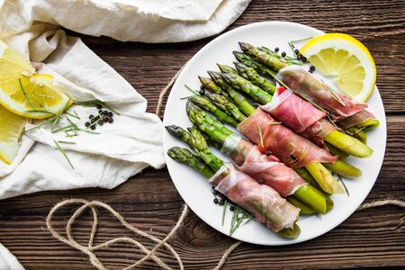 Appetizing italian food - cooked asparagus with meat - appetizer on plate, top view