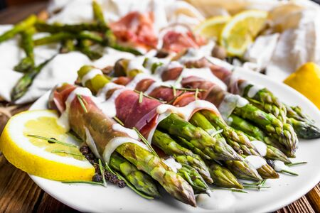 Fresh cooked green asparagus with sauce and ham, italian food concept
