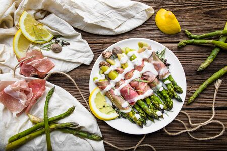 Cooked asparagus, italian appetizer with prosciutto ham and vegetables, food on table, top view