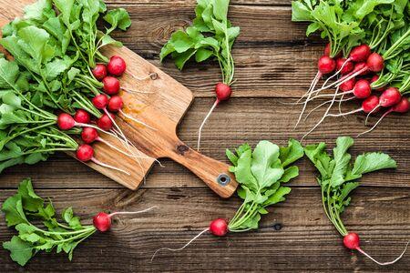 Fresh red radish bunch on wooden on table. Freshly harvested garden radishes. Organic vegetable harvest. Фото со стока