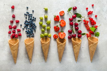 Ice cream cones with fruits. Fresh berry fruit, top view of strawberry, blueberry, raspberry and currant 版權商用圖片