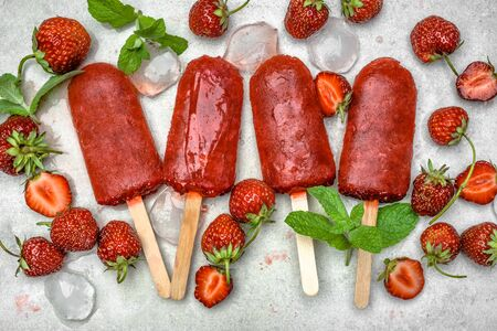 Homemade popsicles with fruits. Strawberry ice lollies on sticks, top view, flat lay Stock Photo