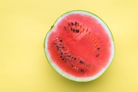 Slice of fresh watermelon isolated on yellow background