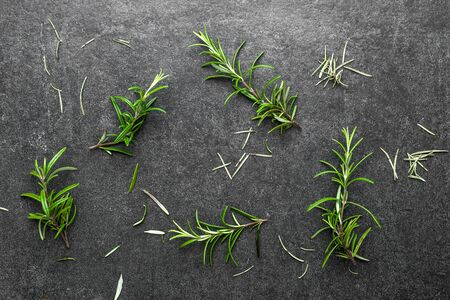 Fresh rosemary. Background with freshly harvested rosemary herbs on black slate. Reklamní fotografie