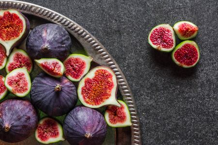 Fresh fig fruits. Blue figs slices on plate.