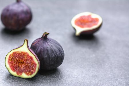 Fresh fig fruits. Whole and sliced figs on dark background.