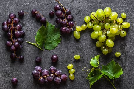 Assorted grapes. Red and green grape on dark background