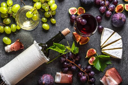 Food background. Glasses of wine and snack set: fresh fruits, cheese appetizer and wine bottle, top view.
