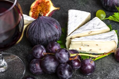 Fruit and wine snack. Camembert cheese, wine, grape and figs, closeup. 写真素材