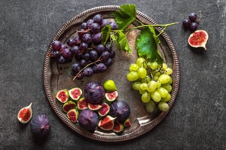 Fresh fruits on plate. Assorted grape and purple figs. Healthy food, vegan diet concept.