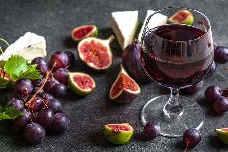 Glass of red wine and appetizers. French cheese, figs and grapes. Wine and cheese tasting.