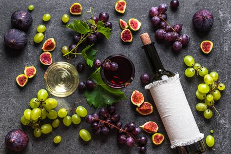 Assorted fruit and wine. Glasses and bottle of wine and grapes, flat lay, overhead.