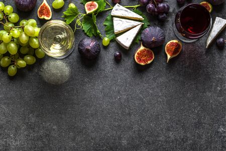 Glasses of red and white wine with cheese, grapes and figs Stockfoto
