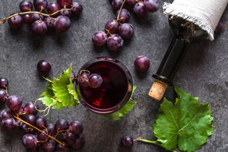 Red wine and grapes. Glass of wine and bottle on black background, top view, flat lay