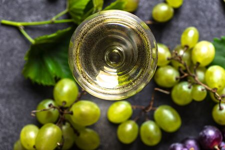 Fresh green grape and white wine glass, closeup, top view