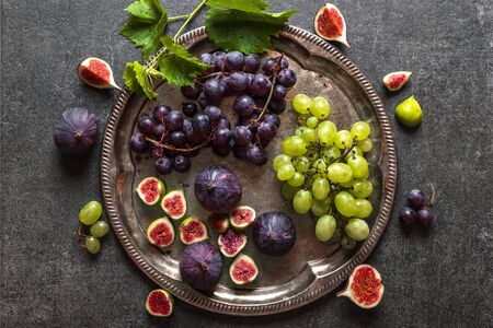 Healthy diet background. Raw organic fruits, fresh figs, red and green grapes on plate. 写真素材
