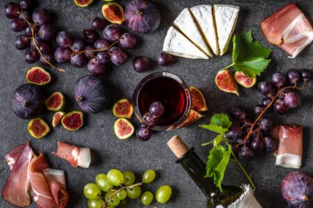 Food background. French appetizers for wine: cheese, figs and grapes.