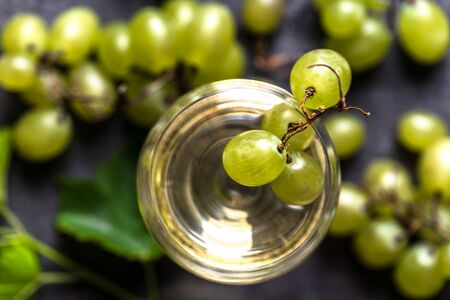Fresh fruit and wine. Glass of white wine, top view.