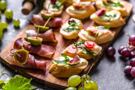 Assorted brushetta - italian apetizer or traditional spanish tapas for sharing. Party food on catering platter. Antipasti with meat, cheese and fruits.