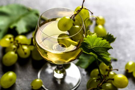White wine glass and fresh grapes on dark background