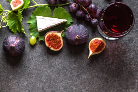 Glass of red wine and appetizers: french cheese, figs, grapes.
