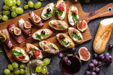 Traditional spanish tapas, wine snack set - food from spain or italian antipasti: bruschetta with cheese, meat and fruits. Cold appetizers and wine glasses.