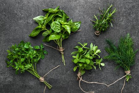 Assorted garden fresh herbs, top view on dark slate