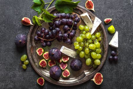 Wine snack set, fruit and cheese - french appetizer on platter, top view Zdjęcie Seryjne
