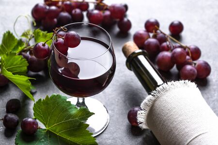 Glass of wine with red grapes and wine bottle on dark background