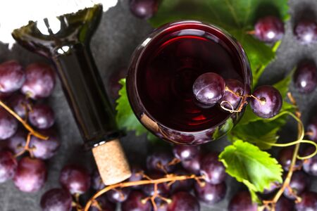Grape wine background. Red wine glass and bottle with cork. Zdjęcie Seryjne