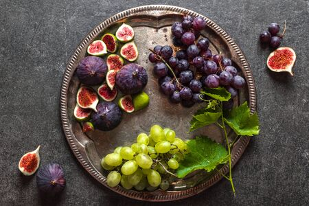 Fresh fruits, different organic fruit on plate - grapes and figs. Healthy diet concept.