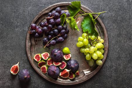 Fresh fruits, assorted organic fruit - figs and grapes on plate. Healthy food concept.