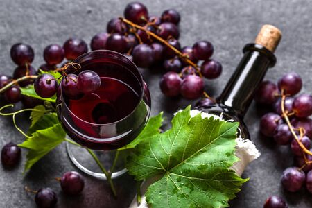 Red wine and grapes. Glass of wine and bottle on black background
